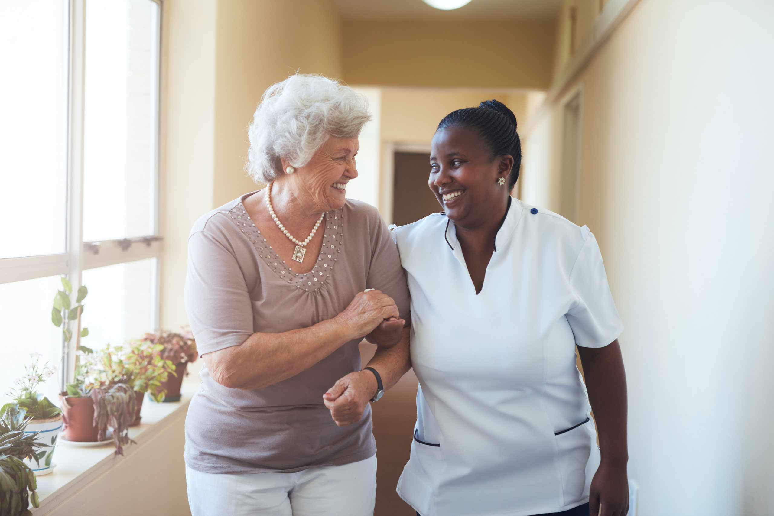 Belleview Suites at DTC | Smiling home caregiver and senior woman walking together