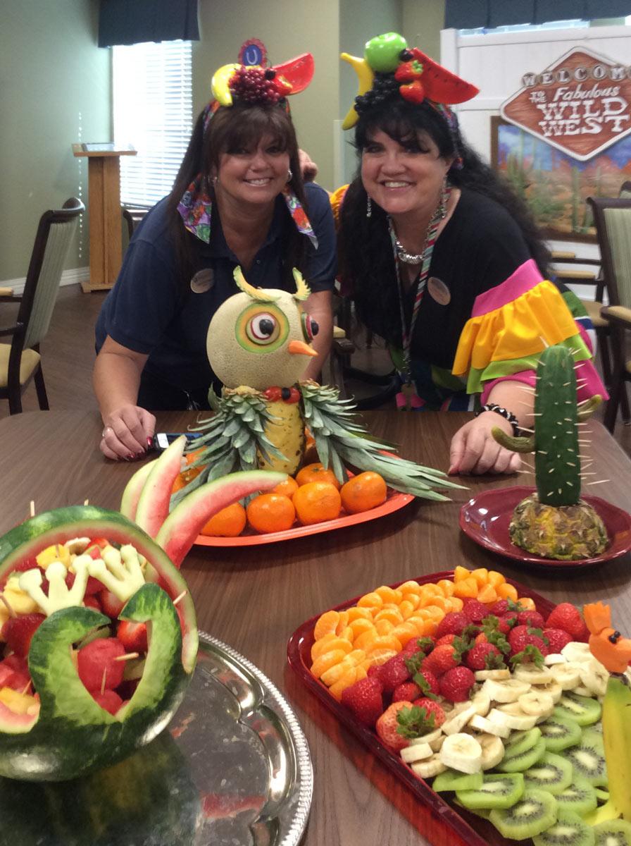 Broadway Mesa Village | Teresa Hadley smiling with her coworker behind sculpted fruit