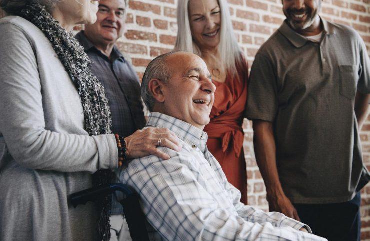Cordata Court | Senior group surrounding man in wheelchair