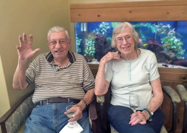 Creston Village | Happy couple waving in front of fish tank