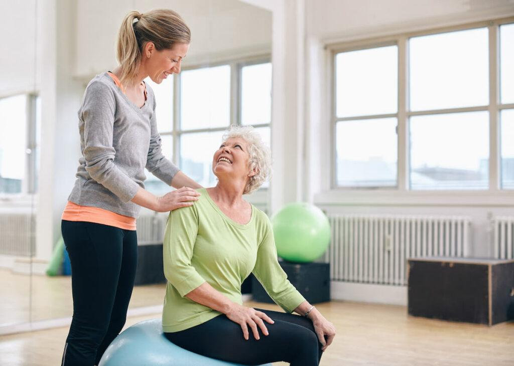 Pegasus Senior Living   Caregiver Assisting Senior with Exercise Activities
