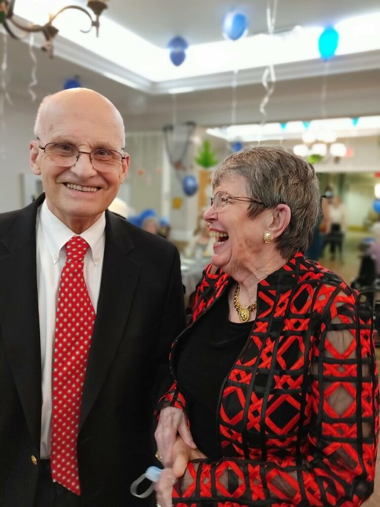 Pegasus Senior Living | Senior couple smiling and laughing at a community event
