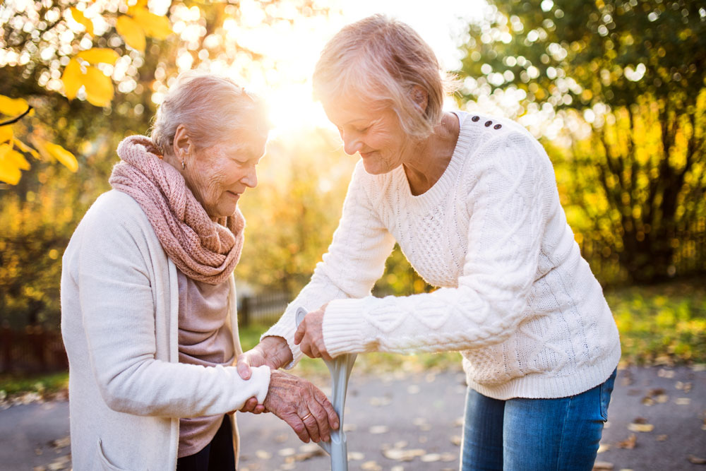 a woman handing a cane to her aging mother
