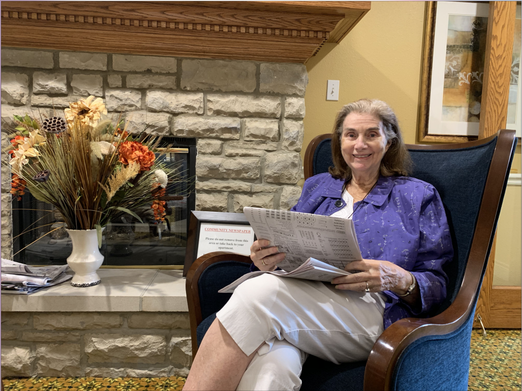 resident at senior living community reading newspaper
