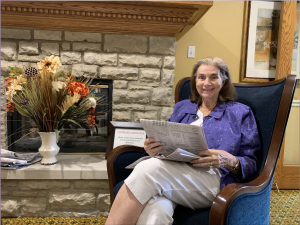 resident at senior living community reading newspaper