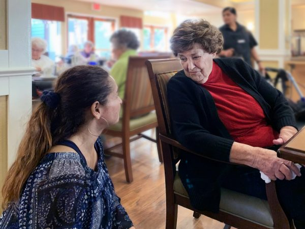 Greenhaven Place | Senior speaking with associate at table