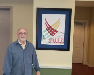 Norm stands with his painting of Laketown Village, a Pegasus Senior Living community in Kenner, LA.