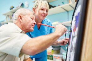 Pegasus Senior Living | Senior painting with associate