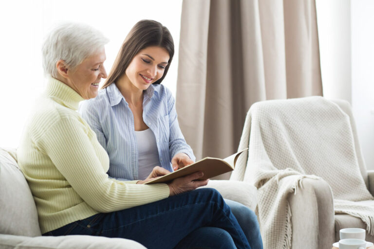 Pegasus Senior Living | Senior reading with associate