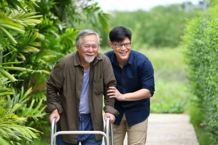 The Courtyards at Mountain View | Senior man using walker with the help of associate