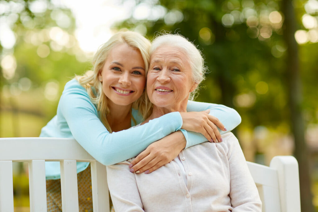 The Farrington at Tanglewood | Senior women and her daughter hugging outside on a bench