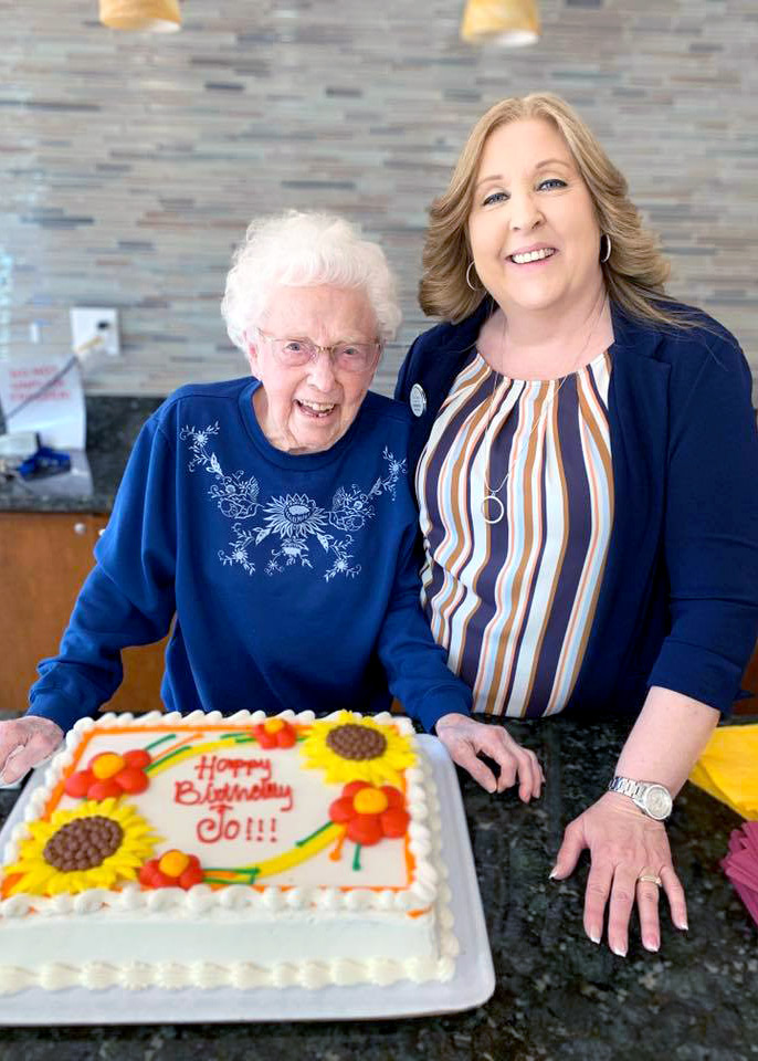 Pegasus Senior Living | Resident and associate with birthday cake