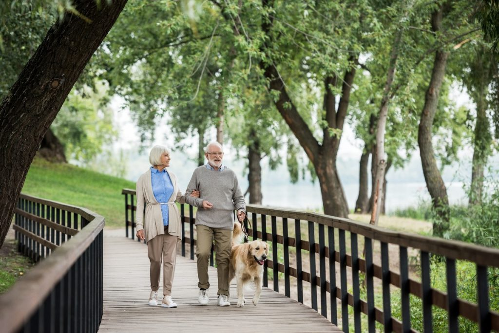 senior couple walking dog along bridge in beautiful community