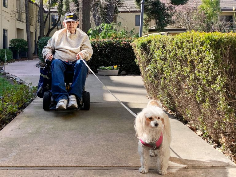 The Oaks at Inglewood | Resident riding across sidewalk with mobility scooter and dog