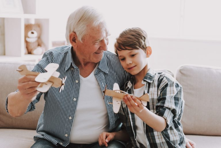 Pegasus Senior Living   Senior flying model planes with his grandson
