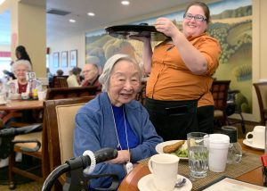 The Village at Rancho Solano | Senior woman served by associate at table