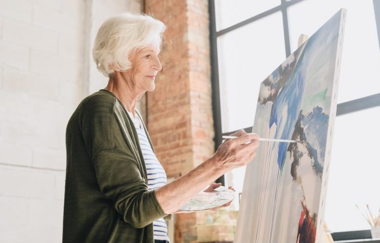 Town Village Crossing | Senior woman painting a picture