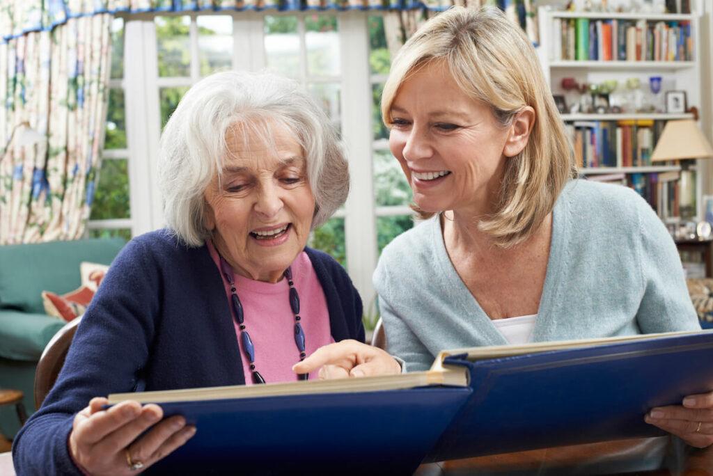 Pegasus Senior Living | Senior woman and her daughter looking though photo album