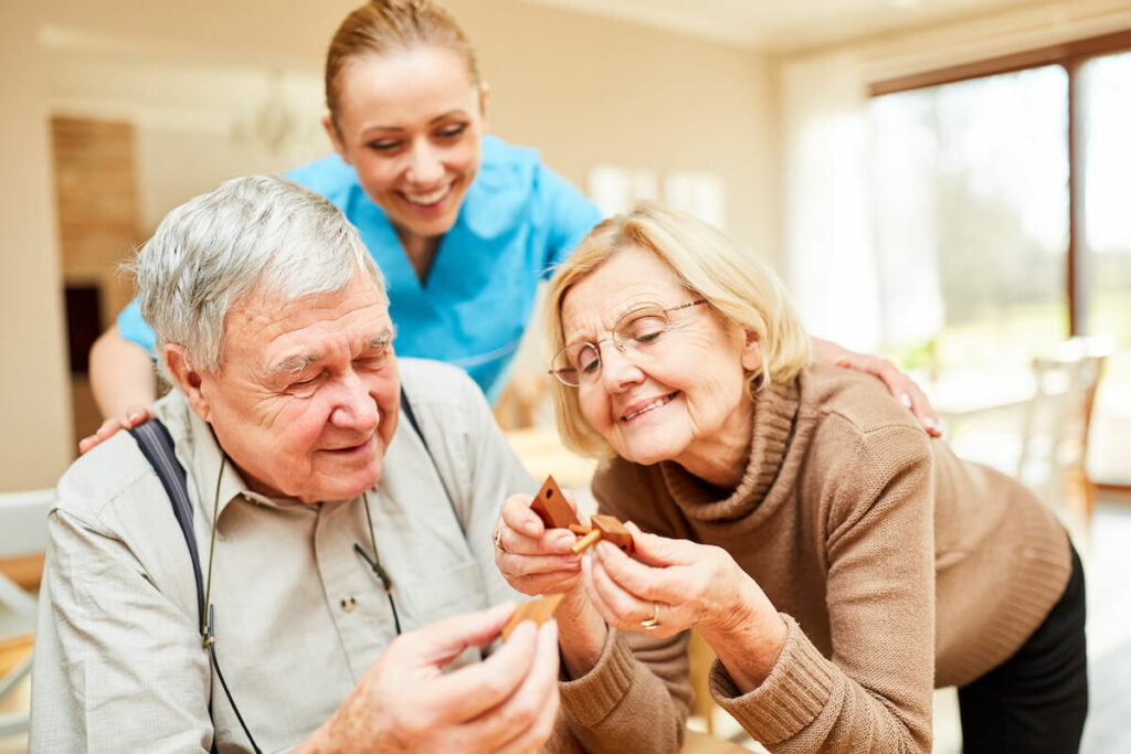 Whispering Winds of Apple Valley   Caregiver assisting seniors with memory care activities