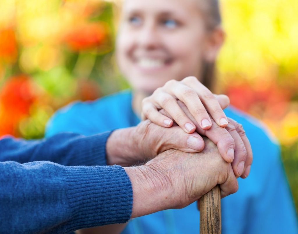 Pegasus Senior Living | Senior holding hands with caregiver