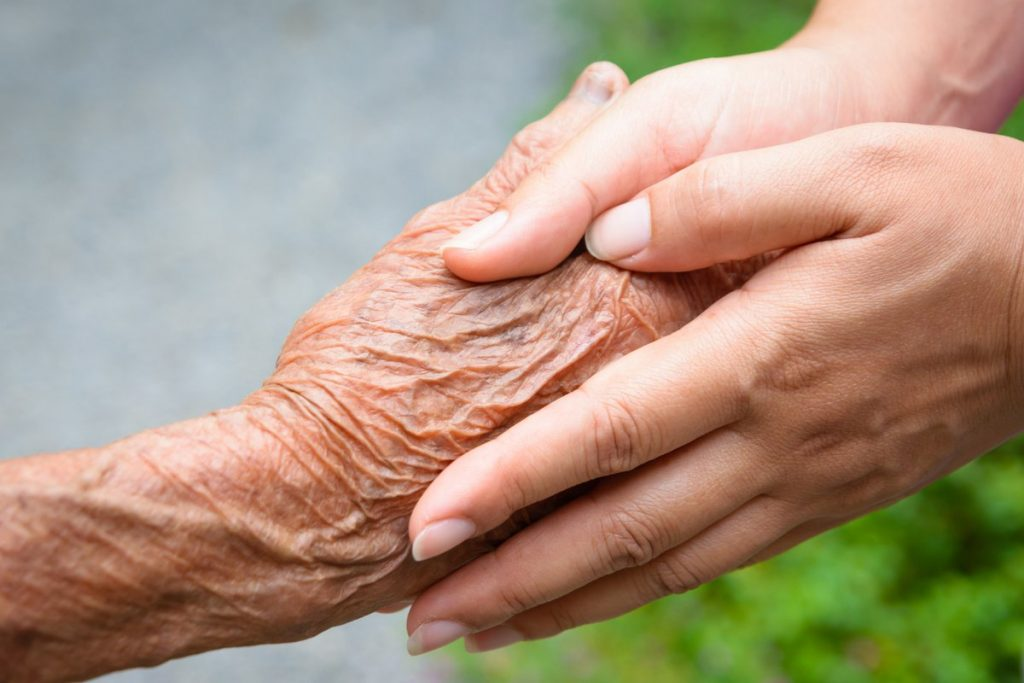 close up of senior's hand held in hands of young woman