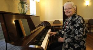 senior woman at piano, smiling
