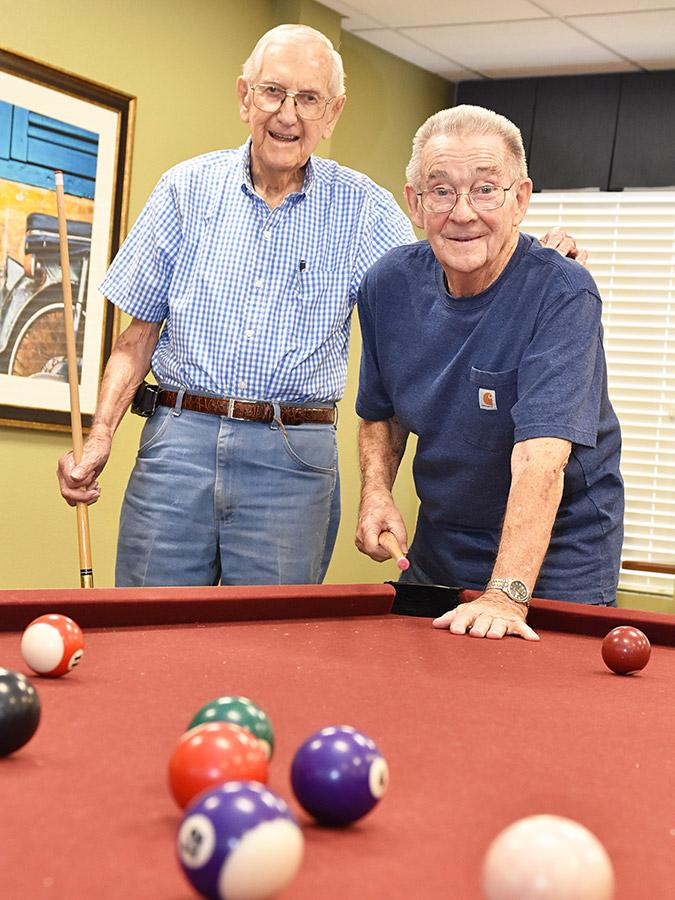 two senior men playing pool at a Pegasus Senior Living community