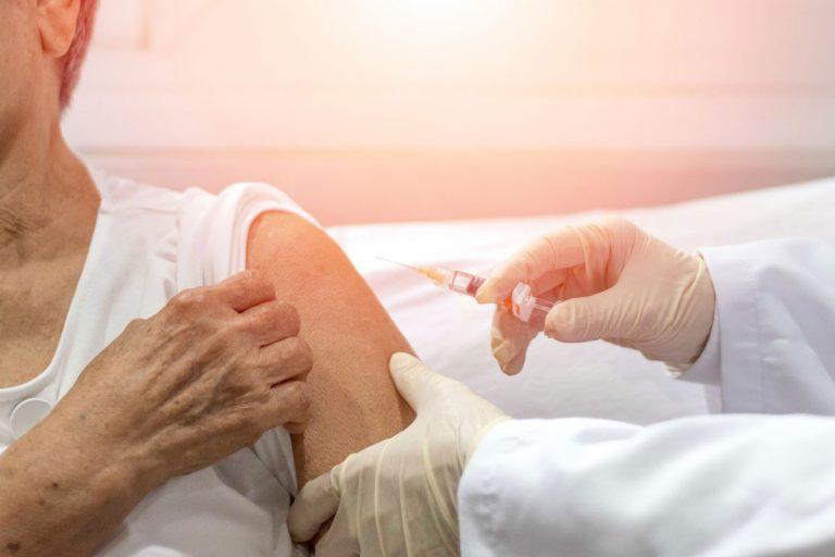 senior woman receives flu shot
