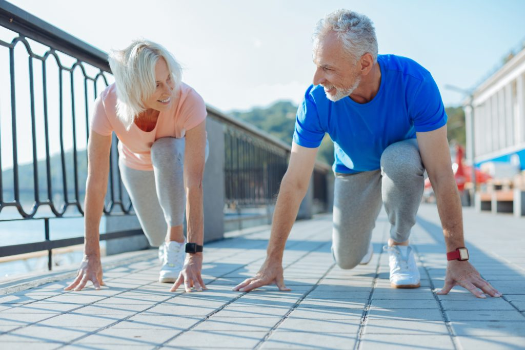 two seniors lunging, preparing for a foot race
