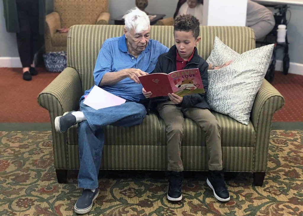 Senior man reading to a boy at Historic Roswell Place, Roswell, GA