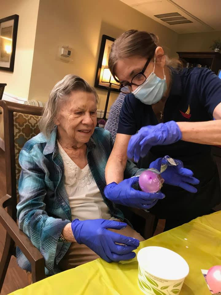 Pegasus Senior Living | Associate helping resident with craft