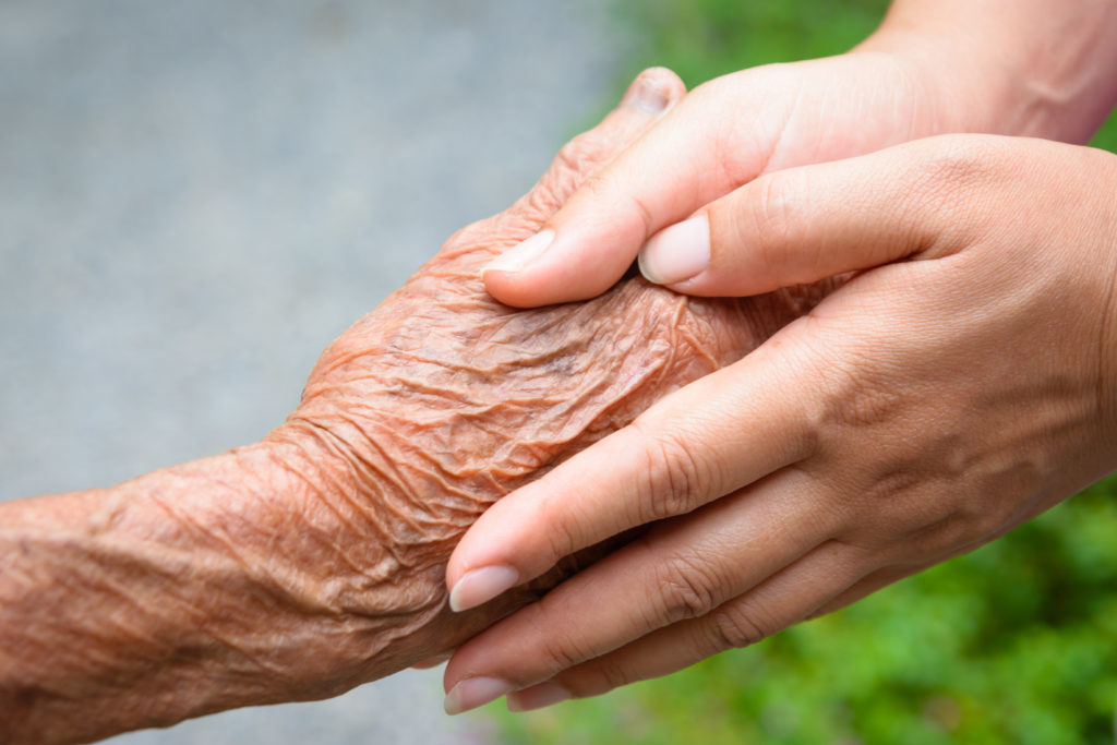 Pegasus Senior Living | Senior holding hands with loved one