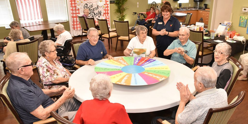 Teresa Hadley, Life Enrichment Director, leads a group of residents in a game at Broadway Mesa Village, Mesa, AZ