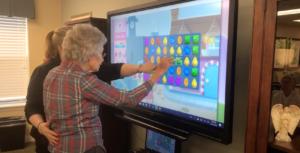 Pegasus Senior Living | Senior playing Candy Crush with associate on SmartBoard