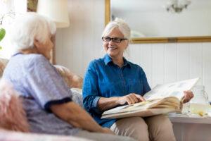 Pegasus Senior Living | Senior looking at photo album with memory care associate in apartment