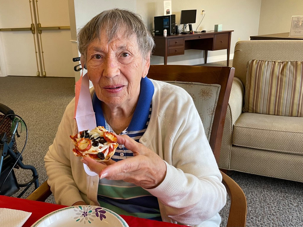Pegasus Senior Living | Senior woman eating pizza